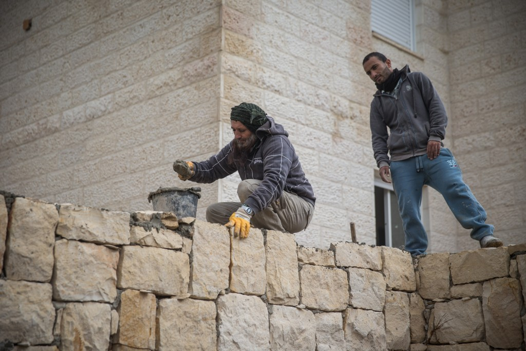 "Palestinian construction workers at a site in Beitar Illit, using the ""ancient methods,"" berated by Bank of Israel Gov. Karnit Flug. (Nati Shohat/Flash90)"