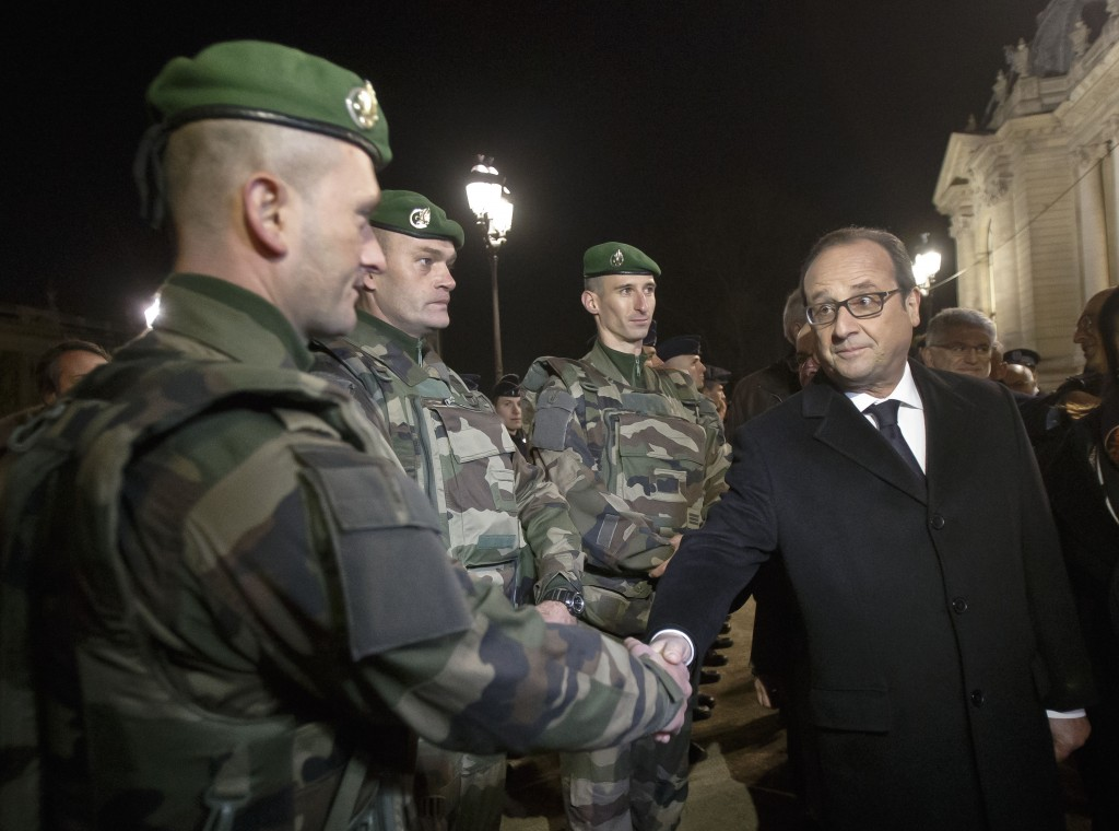 France's President Francois Hollande, right, shakes hands with a foreign legionnaire as he visits the security measures at the Champs Elysees in Paris, Thursday, Dec 31, 2015. (AP Photo/Michel Euler, Pool)