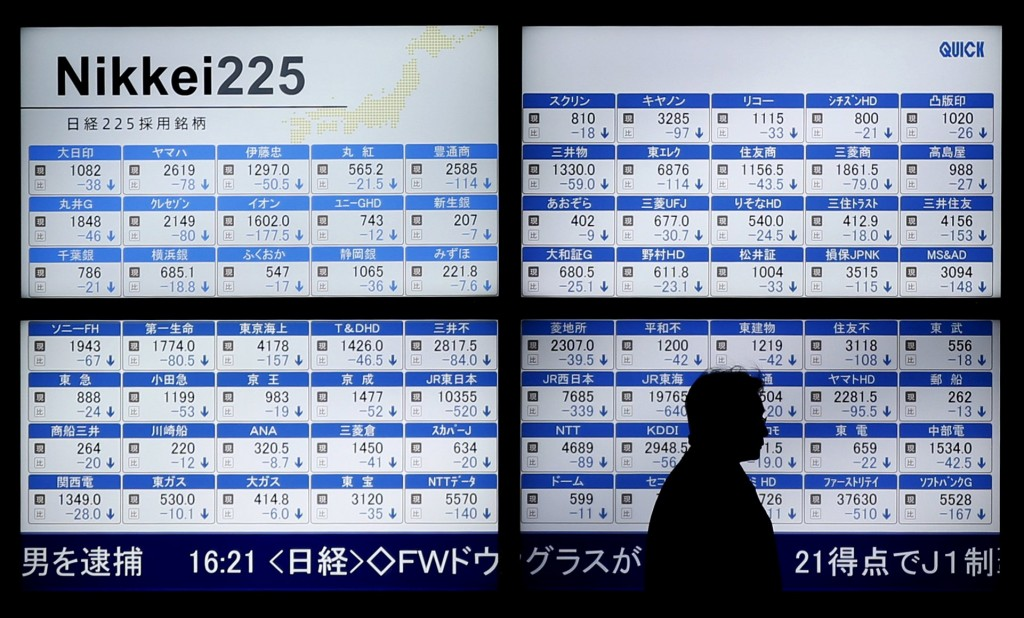 A man walks past an electronic board showing Japan's Nikkei 225 outside a brokerage in Tokyo, Japan January 12, 2016. Japan's Nikkei fell 2.7 percent after a market holiday on Monday, closing at its lowest in nearly a year, while U.S. stock mini futures were in the red pointing to a weak start. REUTERS/Toru Hanai