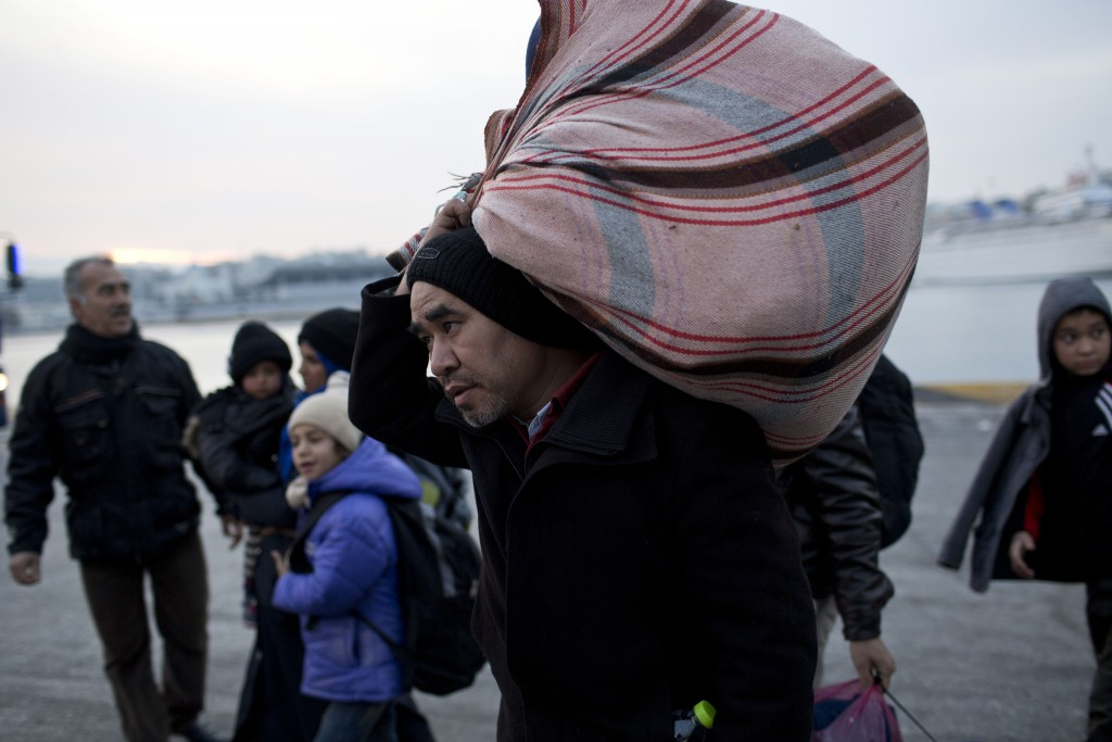 Refugees and migrants disembark from a Ferry at the Athens' main port of Piraeus, early Wednesday, Jan 27, 2016. Greek authorities say a total of seven bodies, including those of two children, have been recovered from the sea off the eastern Aegean island of Kos after a boat carrying migrants or refugees sank early Wednesday.(AP Photo/Petros Giannakouris)