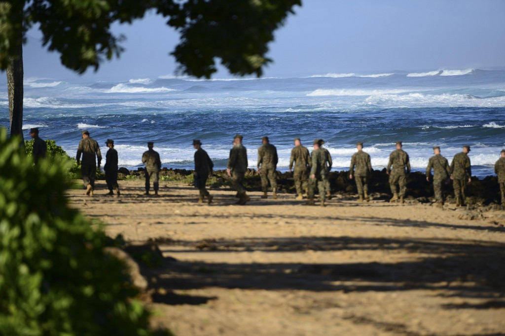 A group of Marines walk the beach outside the Haleiwa Incident Command Post in Haleiwa, Hawaii, during search efforts for 12 missing Marines, in this handout photo taken January 18, 2016. The U.S. Coast Guard said on Tuesday it had suspended its search for 12 Marines who have been missing since two military helicopters collided last week off Hawaii's Oahu island. Picture taken January 18, 2016. REUTERS/U.S. Coast Guard/Petty Officer 1st Class Levi Read/Handout via Reuters THIS IMAGE HAS BEEN SUPPLIED BY A THIRD PARTY. IT IS DISTRIBUTED, EXACTLY AS RECEIVED BY REUTERS, AS A SERVICE TO CLIENTS. FOR EDITORIAL USE ONLY. NOT FOR SALE FOR MARKETING OR ADVERTISING CAMPAIGNS