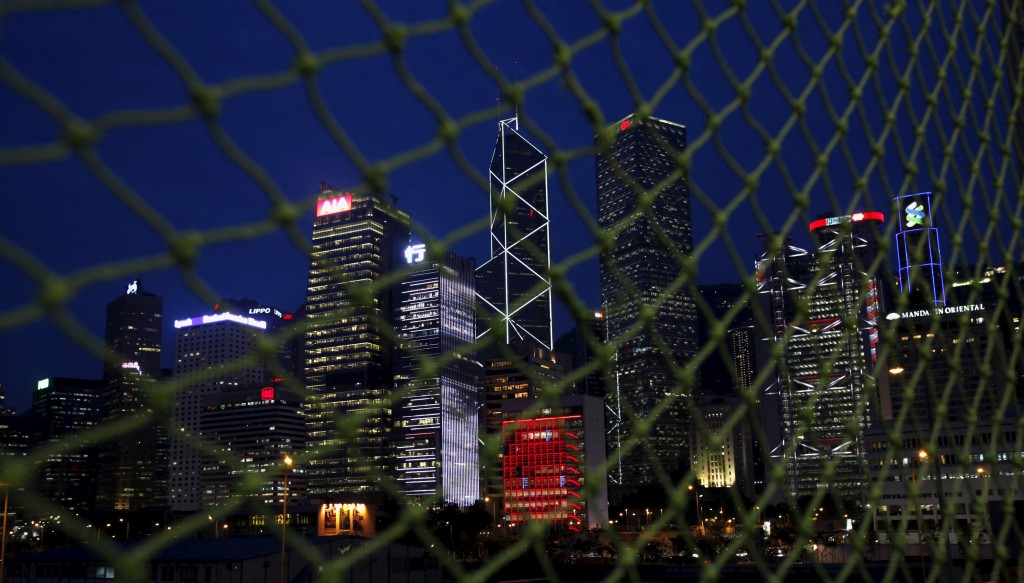 Skyscrapers at Hong Kong's central business district (L-R) AIA Central, CCB Tower, Bank of China Tower, City Hall (in red), Cheung Kong Centre, HSBC headquarters and Standard Chartered Bank are seen behind a net near a construction site moments after sunset in this June 10, 2014 file photo. Chinese stock investors are finally seeing value in domestic shares, but there's a twist: instead of wading back onto battered onshore exchanges, they've gone shopping for bargains in Hong Kong. REUTERS/Bobby Yip/Files