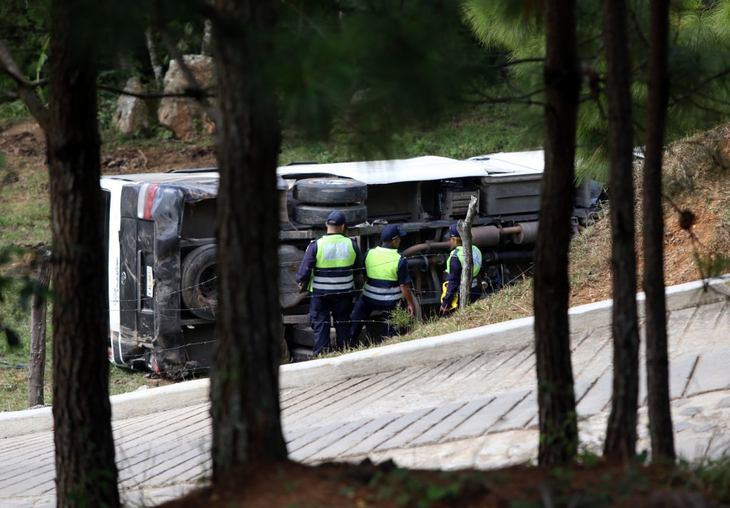 This photo courtesy of El Heraldo de Honduras newspaper shows a bus on its side along the highway between the town of San Juancito and the capital city of Tegucigalpa, Honduras, Wednesday, Jan. 13, 2016. Two New York college students and a U.S. health-care worker died Wednesday in this Central American nation when their bus crashed while taking them to the airport to fly home after a volunteer mission helping poor Hondurans. (El Heraldo de Honduras via AP)