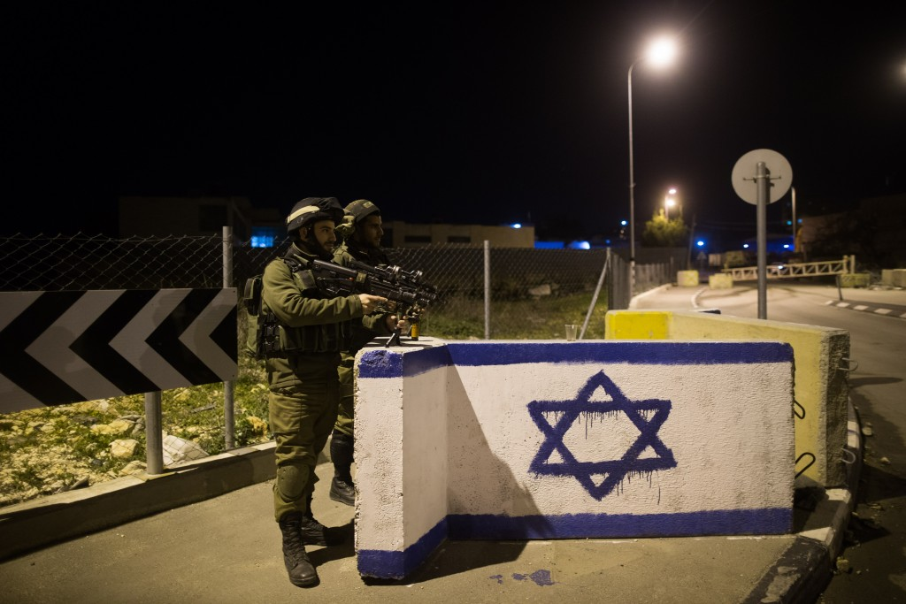 Israeli soldiers stand guard at a junction near the entrance to Kiryat Arba on Sunday night. (Yonatan Sindel/Flash90)
