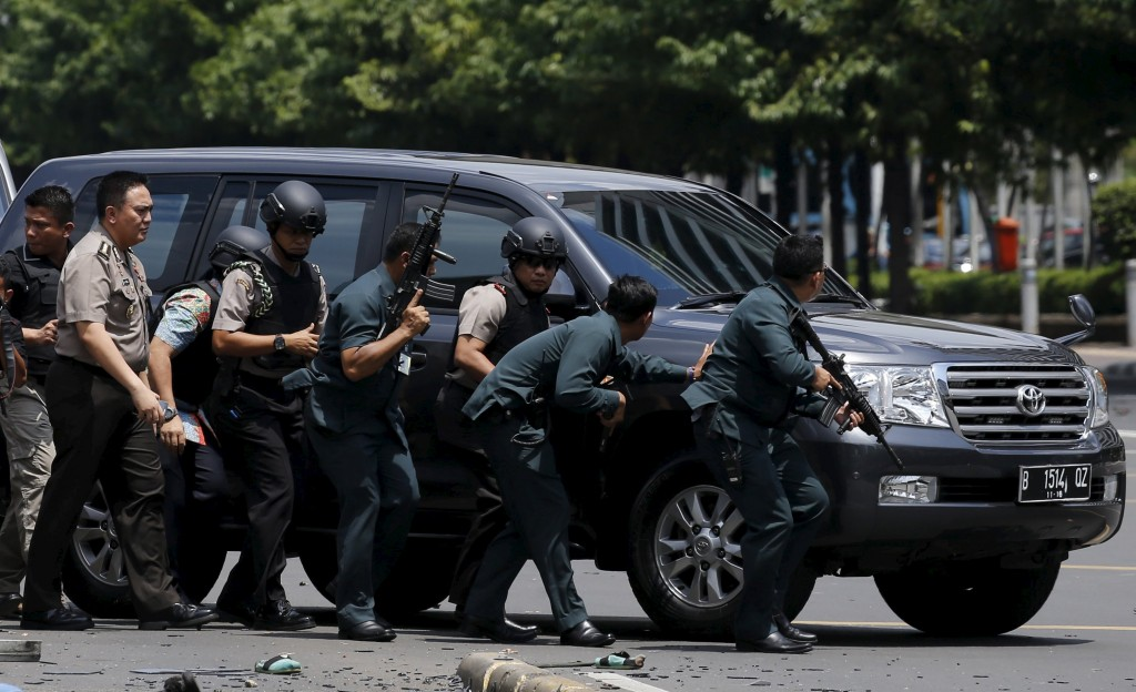 Indonesian police hold rifles while walking behind a car for protection in Jakarta January 14, 2016. Several explosions went off and gunfire broke out in the center of the Indonesian capital on Thursday and police said they suspected a suicide bomber was responsible for at least one the blasts. REUTERS/Beawiharta TPX IMAGES OF THE DAY