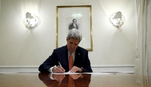 U.S. Secretary of State John Kerry signs a series of documents, including the certification to the U.S. government that International Atomic Energy Agency (IAEA) had certified Iran's compliance in their report and waivers to implement the lifting of the U.S. Congressional nuclear-related sanctions as outlined in the Joint Comprehensive Plan of Action (JCPOA), in Vienna January 16, 2016. REUTERS/Kevin Lamarque