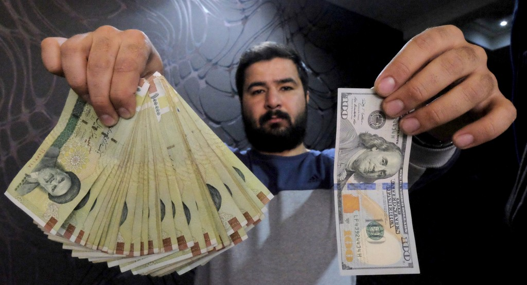 A money changer poses for the camera with a U.S dollar (R) and the amount being given when converting it into Iranian rials (L), at a currency exchange shop in Tehran's business district, Iran, January 20, 2016. REUTERS/Raheb Homavandi/TIMA ATTENTION EDITORS - THIS IMAGE WAS PROVIDED BY A THIRD PARTY. FOR EDITORIAL USE ONLY.
