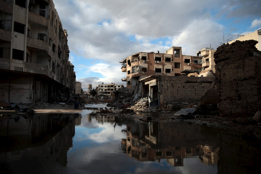 Damaged buildings are reflected on water flooding a street in Jobar, a suburb of Damascus, Syria January 23, 2016. REUTERS/Bassam Khabieh