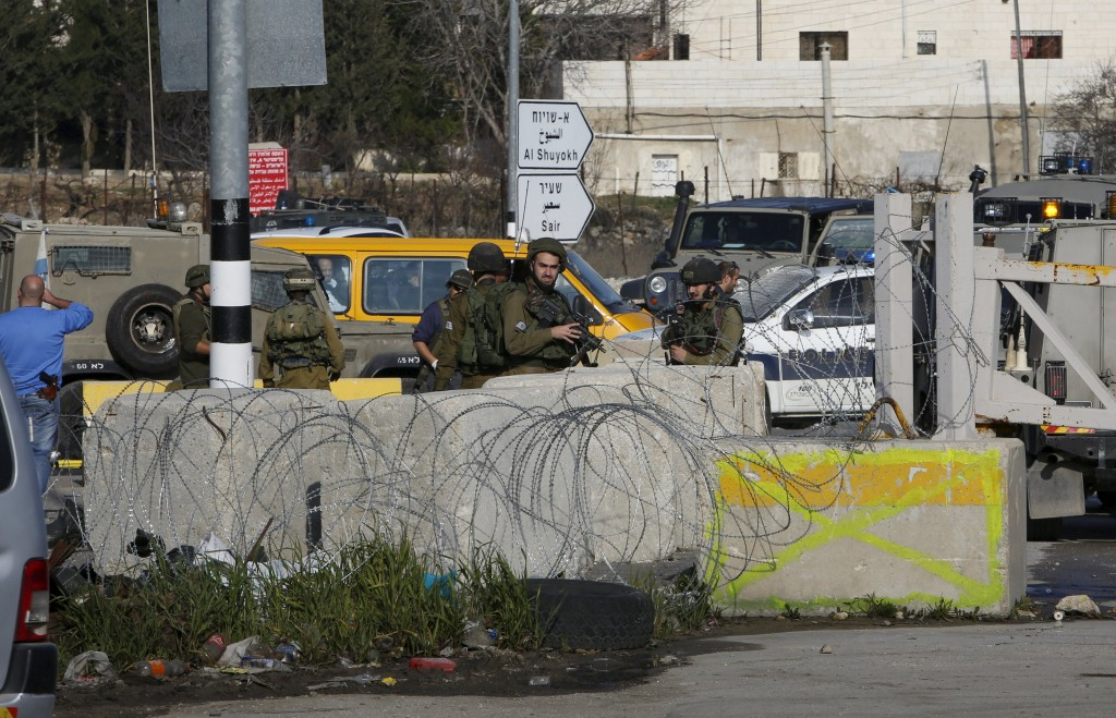 Israeli soldiers stand guard near the scene where Israeli military said a Palestinian, who tried to stab a soldier, was shot dead by Israeli troops, in the West Bank city of Hebron January 12, 2016. An Israeli military spokeswoman said troops fatally shot a Palestinian who tried to stab a soldier in the West Bank city of Hebron. Palestinian officials gave his age as 17 and said another Palestinian was killed by Israeli soldiers in the city. The Israeli military had no immediate information about a second fatality in Hebron. REUTERS/Mussa Qawasma