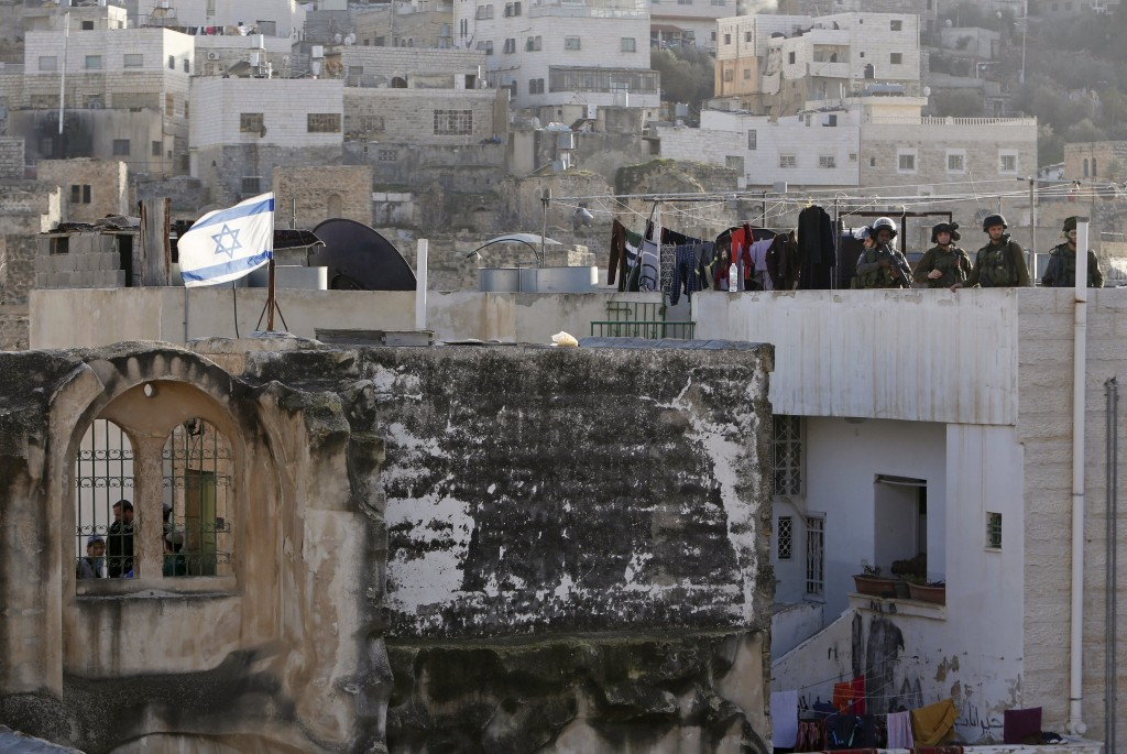 Israeli soldiers and border police stand guard as Israeli settlers take over several houses, which are disputed between Palestinians and Israelis, in the West Bank old city of Hebron January 21, 2016. Israeli settlers, escorted by the Israeli army, took over several houses, witnesses said. REUTERS/Mussa Qawasma