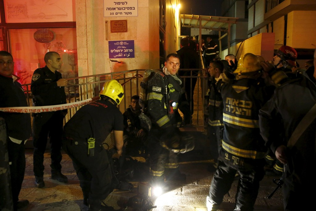 Israeli fire-fighters stand at the entrance to an office building where the offices of B'Tselem is located, in Jerusalem January 10, 2016. A fire broke out on Sunday in the Jerusalem offices of one of Israel's leading human rights groups and authorities were checking whether it was set deliberately, a police spokeswoman said. REUTERS/Ronen Zvulun