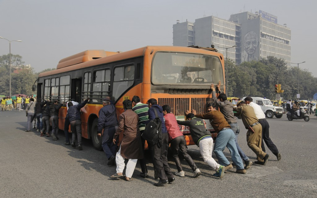 Passengers and traffic policemen push a bus after it broke down at a traffic intersection on the first day of a two-week experiment to reduce the number of cars to fight pollution in New Delhi, India, Friday, Jan. 1, 2016. (AP Photo/Altaf Qadri)