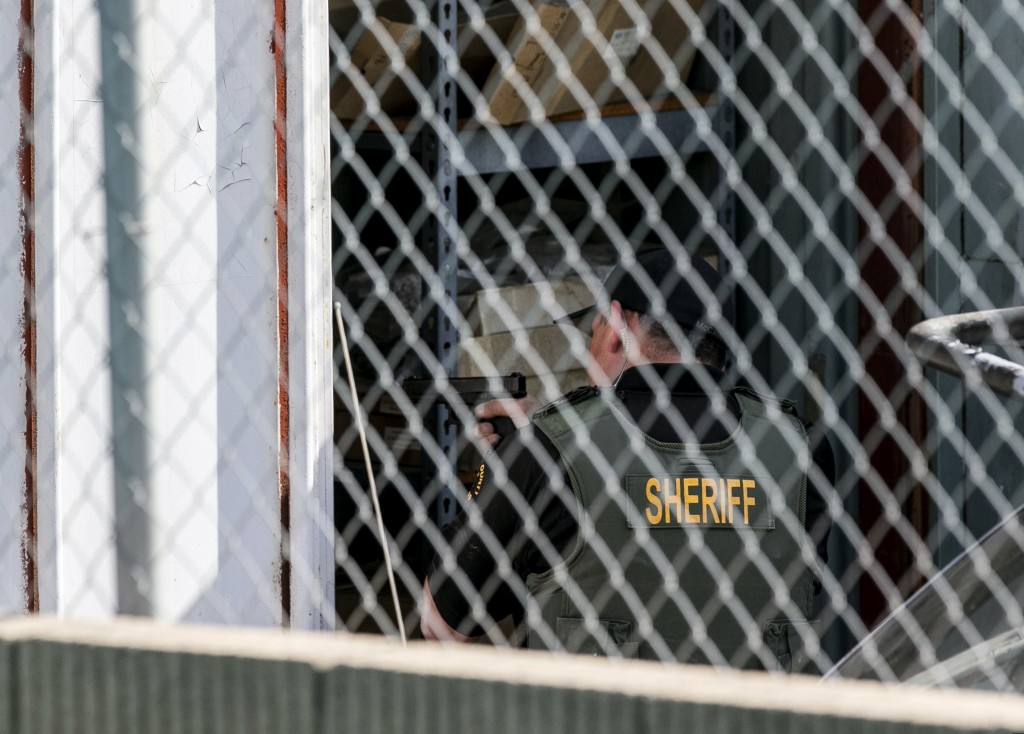 A Orange County Law enforcement agent points his gun inside a container while conducting a search for additional suspects at the back
