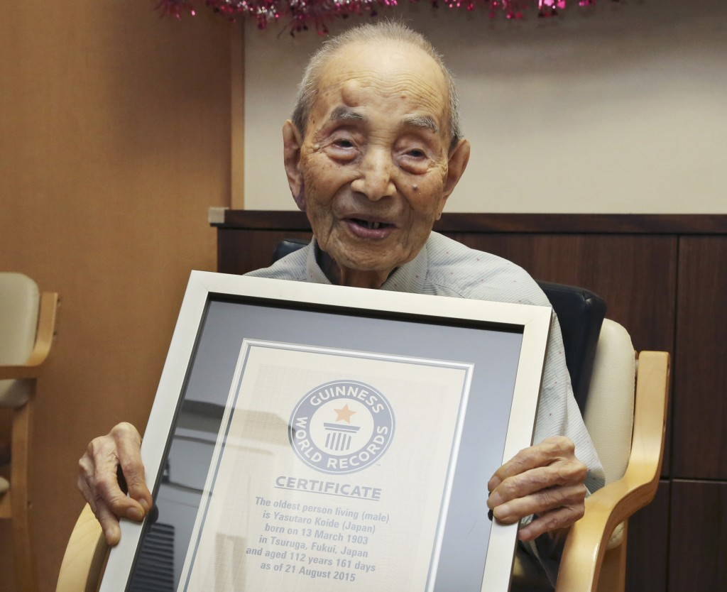 FILE - In this Aug. 21, 2015, file photo, Yasutaro Koide, 112, holds the Guinness World Records certificate as he is formally recognized as the world's oldest man at a nursing home in Nagoya, central Japan. Koide, who was born on March 13, 1903, has died on Tuesday, Jan. 19, 2016, two months short of his 113th birthday. (AP Photo/Koji Sasahara, FIle)
