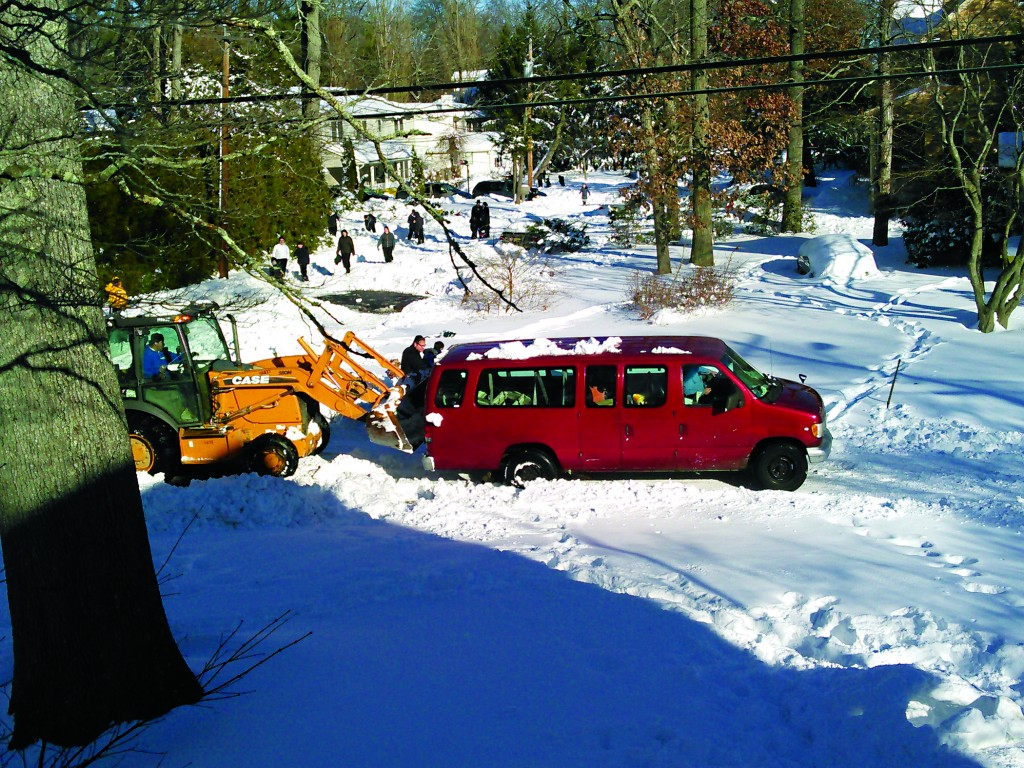 A van getting a boost from a bulldozer during the challenging snow conditions in Lakewood.