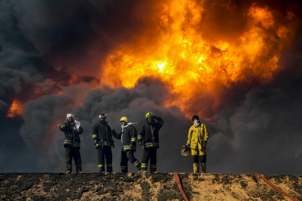 """Firefighters stand while trying to put out a fire in an oil tank in the port of Es Sider, in Ras Lanuf, Libya, in this file picture taken January 6, 2016. The attacks against Libya's biggest oil terminals were lethal and sustained. The last two weeks have seen suicide bombings, huge fires at storage tanks, and a hole blown in a major pipeline. The oil ports of Es Sider and Ras Lanuf had been closed for more than a year, and the Islamic State militants advancing on them backed off after three days of shelling and clashes. But the escalation of violence in Libya's coastal """"oil crescent"""" has underscored the threat to an energy industry that, despite the political chaos plaguing the country, still provides vital income to the state. REUTERS/Stringer/Files FOR EDITORIAL USE ONLY. NO RESALES. NO ARCHIVE."""