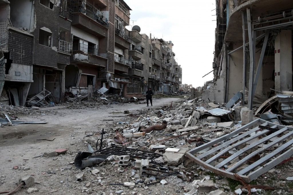 A Free Syrian Army fighter walks past damaged buildings in Jobar, a suburb of Damascus, Syria January 23, 2016. REUTERS/Bassam Khabieh