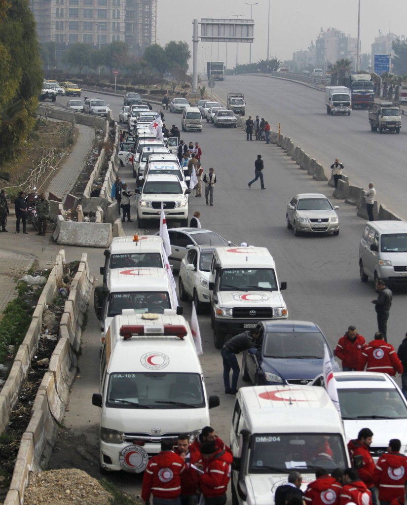 A convoy consisting of Red Cross, Red Crescent and United Nation (UN) gather before heading towards to Madaya from Damascus, and to al Foua and Kefraya in Idlib province, Syria January 11, 2016. Aid convoys headed for a besieged Syrian town where thousands are trapped and the United Nations says people are reported to have died of starvation. Trucks headed for Madaya, near the Lebanese border, and two villages in the northwest of the country on Monday, the Red Cross said, as part of an agreement between warring sides. REUTERS/Omar Sanadiki