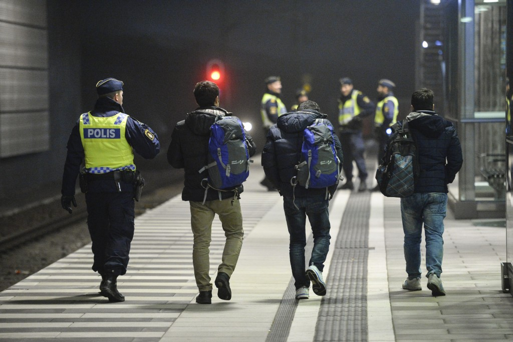 A police officer escorts migrants from a train at Hyllie station outside Malmo, Sweden. Picture taken November 19, 2015. REUTERS/Johan Nilsson/TT NEWS AGENCY TPX IMAGES OF THE DAY ATTENTION EDITORS - THIS IMAGE WAS PROVIDED BY A THIRD PARTY. FOR EDITORIAL USE ONLY. NOT FOR SALE FOR MARKETING OR ADVERTISING CAMPAIGNS. THIS PICTURE IS DISTRIBUTED EXACTLY AS RECEIVED BY REUTERS, AS A SERVICE TO CLIENTS. SWEDEN OUT. NO COMMERCIAL OR EDITORIAL SALES IN SWEDEN. NO COMMERCIAL SALES. TPX IMAGES OF THE DAY