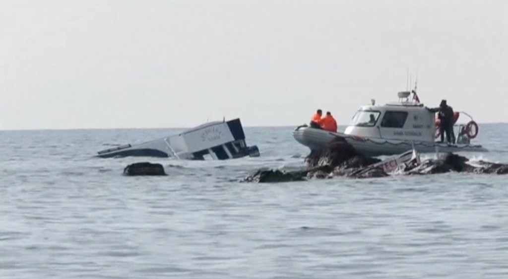 A boat (L) which carried migrants sinks into the sea off Turkey's western coast of Ayvacik, are seen in this still image from video taken January 30, 2016. Almost 40 people drowned and 75 were rescued after a boat carrying migrants to Greece sank off Turkey's western coast on Saturday, according to local officials and the Turkish Dogan news agency. The Turkish coast guard was continuing search and rescue efforts where the 17-metre boat carrying at least 120 people sank off the coast of Ayvacik, a town across from the Greek island of Lesvos, the Dogan news agency reported. REUTERS/Reuters TV