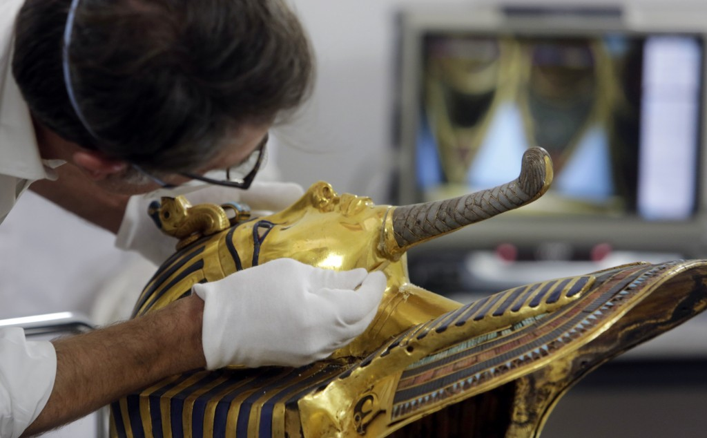 In this Oct. 20, 2015 photo, German restorer Christian Eckmann begins restoration work on the golden mask of King Tutankhamun over a year after the beard was accidentally broken off and hastily glued back with epoxy, at the Egyptian Museum in Cairo. (AP Photo/Amr Nabil, File)