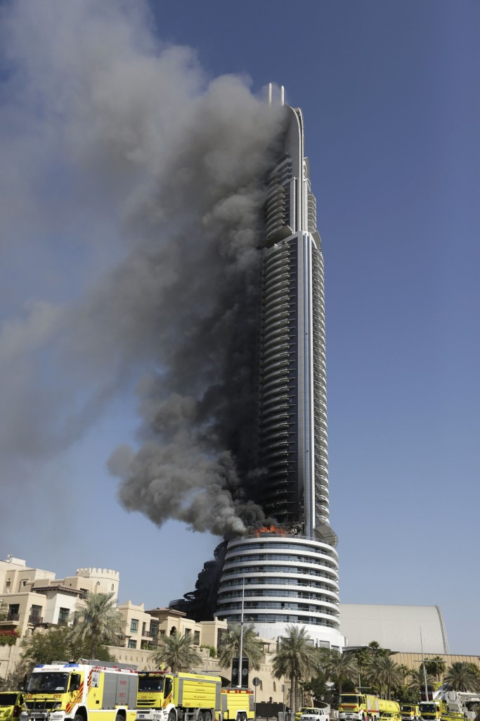 A fire burns on the Address Downtown skyscraper in Dubai, United Arab Emirates on Friday, Jan. 1, 2016. The blaze began Thursday night before Dubai's annual New Year's Eve fireworks show at the Burj Khalifa, the world's tallest building which sits nearby. (AP Photo/Sunday Alamba)
