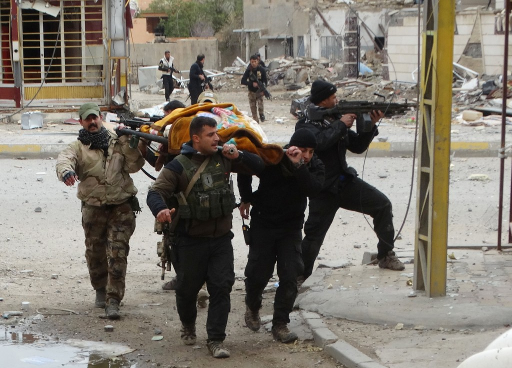 Iraqi security forces and allied Sunni tribal fighters evacuate an injured civilian who was shot by IS terrorists while trying to cross from neighborhoods under control of IS to neighborhoods under control of Iraqi security forces in Ramadi. (AP Photo, File)