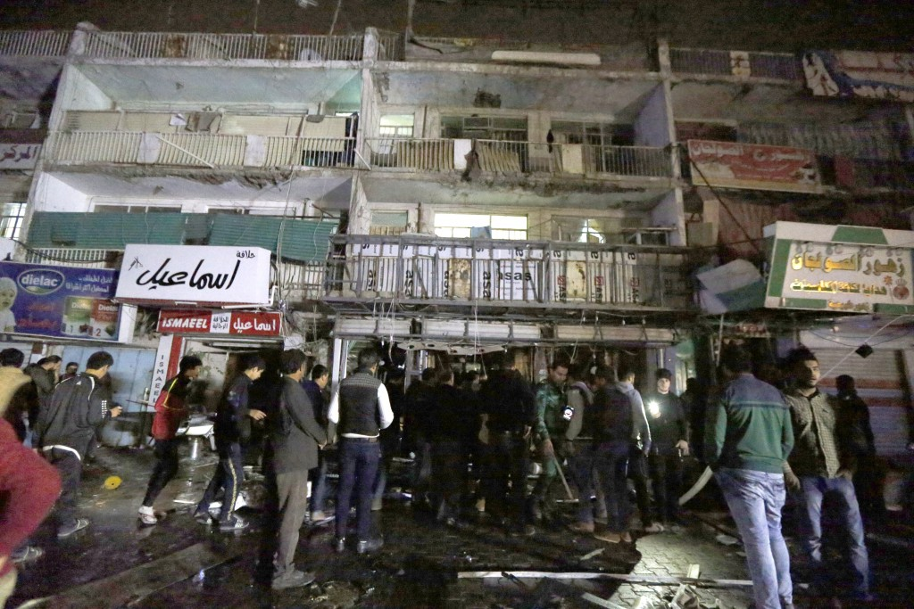 People gather in front of the mall in Baghdad after Monday's attack that left 18 dead. (AP Photo)