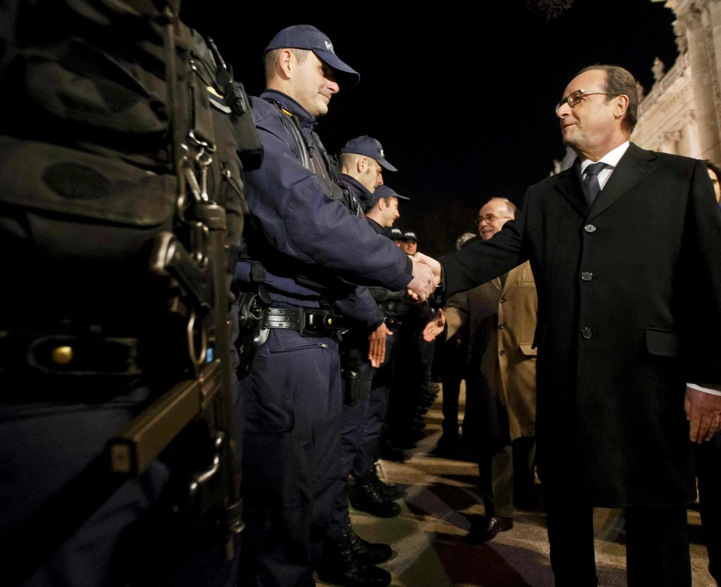 French President Francois Hollande (R) shakes hands with a police officer as he visits security forces near the Champs Elysees Avenue in Paris, France, December 31, 2015.  REUTERS/Michel Euler/Pool