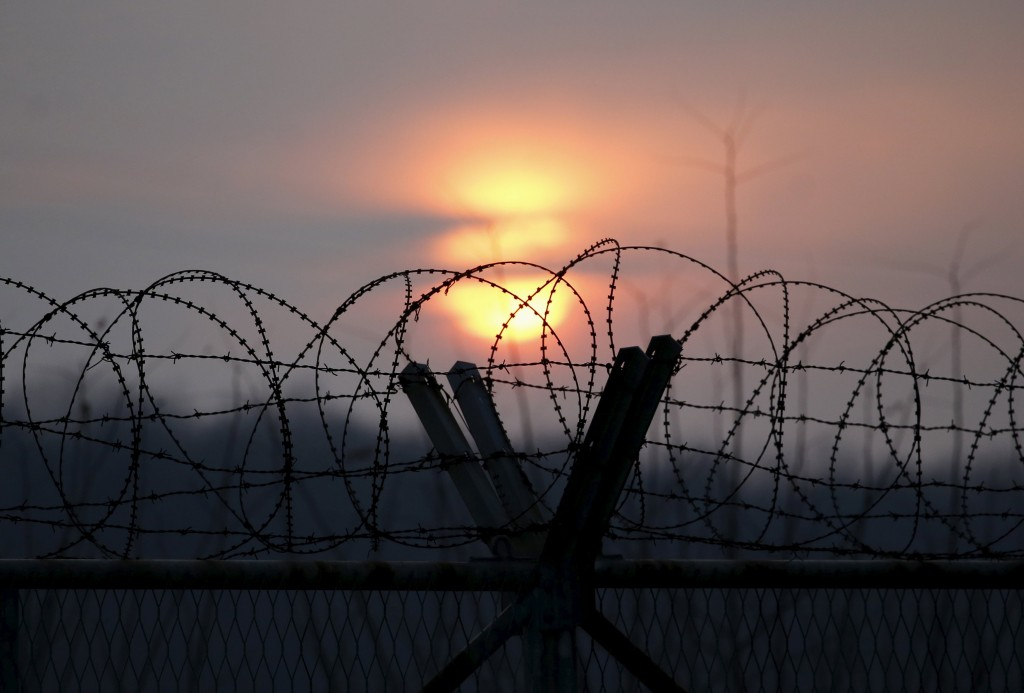 The sun sets behind a barbed wire fence near the demilitarized zone separating the two Koreas in Paju, South Korea, January 6, 2016. REUTERS/Kim Hong-Ji