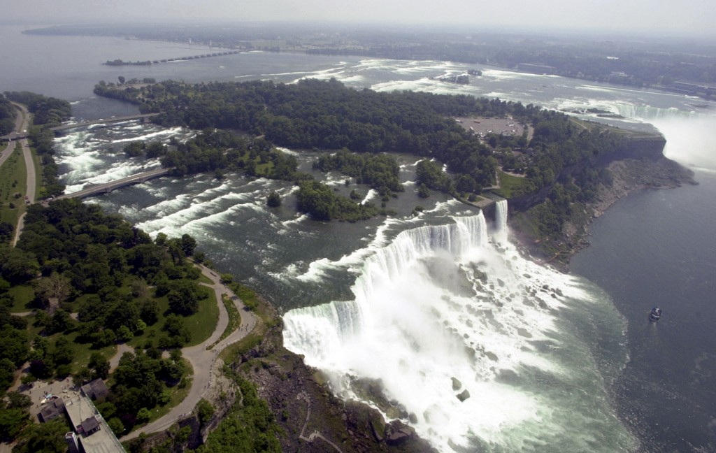 FILE - In this June 14, 2001, file aerial photo, the United States side, foreground, of Niagara Falls is viewed in Niagara Falls, N.Y. New York officials are considering temporarily turning Niagara Falls into a trickle. State officials are holding a public hearing this week to discuss plans for replacing 115-year-old bridges, left, linking the mainland to islands near the brink of the falls. To do so, they might reduce the flow on the American side of the falls by building a temporary structure to redirect Niagara River water to the Canadian side, upper right. (AP Photo/David Duprey, File) Summary