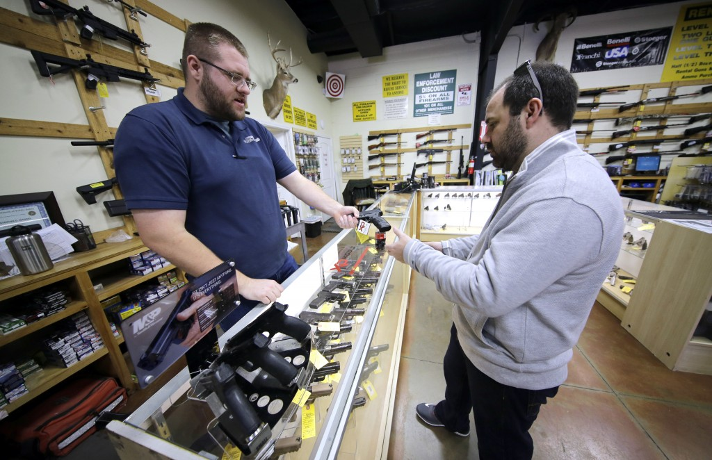 Mike Howse, left, helps David Foley as he shops for a handgun at the Spring Guns and Amo store in Spring, Texas, on Monday. (AP Photo/David J. Phillip)