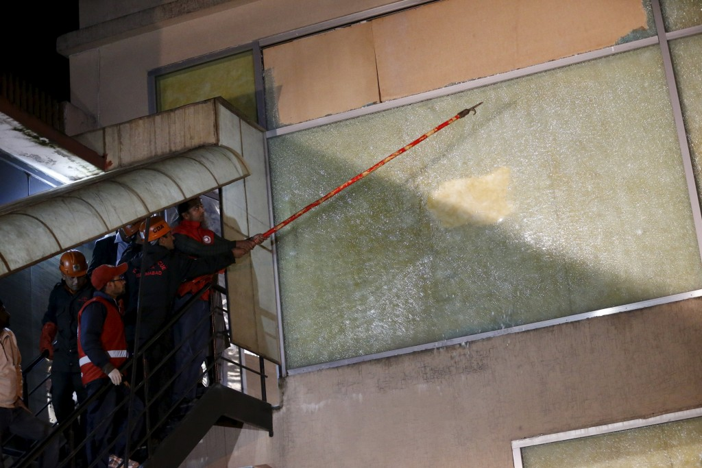 Firemen clear shattered glass at the ARY News offices after a blast injured several people and caused property damage in Islamabad, Pakistan January 13, 2016. REUTERS/Caren Firouz