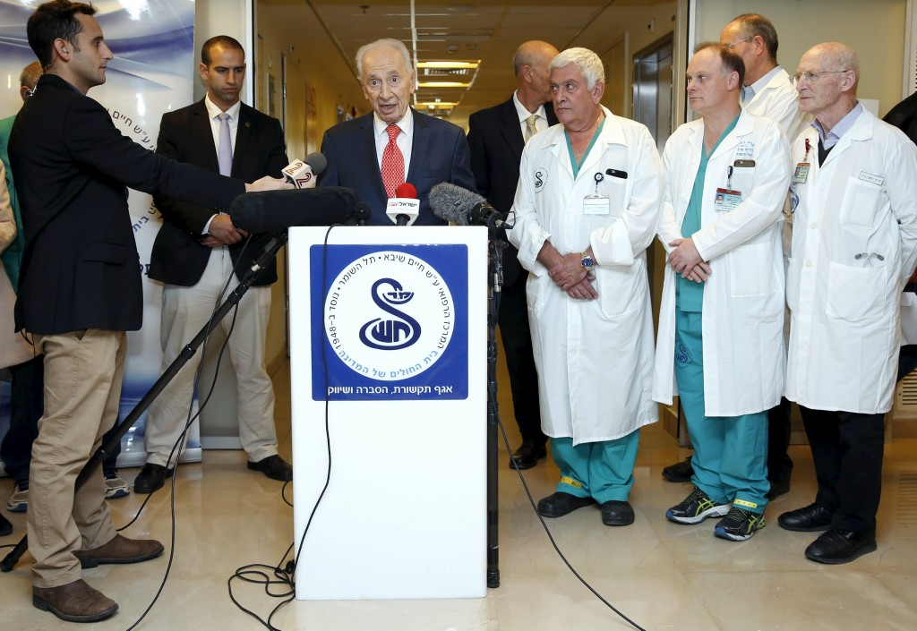 Former Israeli President Shimon Peres (3rd L) delivers a statement to the media as he is discharged from a hospital near Tel Aviv, January 19, 2016. The 92-year-old former prime minister and president successfully underwent minor surgery for a constricted artery that had caused chest pain on January 14, officials said. REUTERS/Baz Ratner