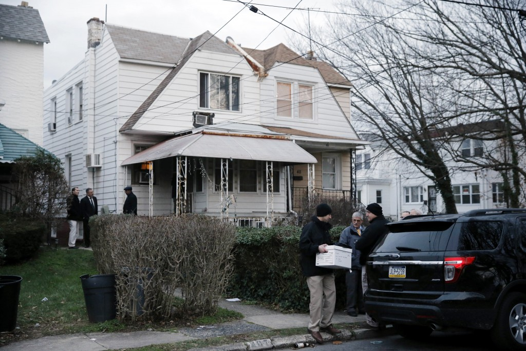 An investigator takes a box from one of the residences where suspect Edward Archer has lived Friday, Jan. 8, 2016, in Yeadon, Pa. Archer accused of ambushing a police officer and firing shots at point-blank range said he was acting in the name of Islam and had pledged allegiance to the Islamic State group, Philadelphia authorities said Friday. (AP Photo/Matt Rourke)