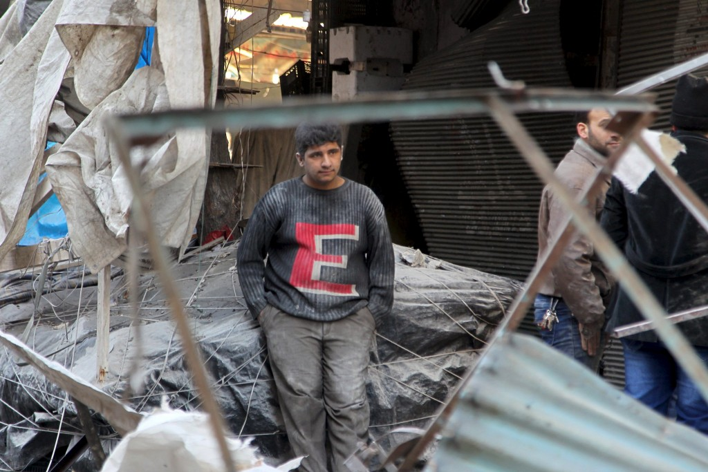 A man rests in a site damaged by what activists said was an airstrike by forces loyal to Syria's president Bashar Al-Assad in al-Sukkari neighborhood of Aleppo, Syria, January 16, 2016. REUTERS/Abdalrhman Ismail        EDITORIAL USE ONLY. NO RESALES. NO ARCHIVE