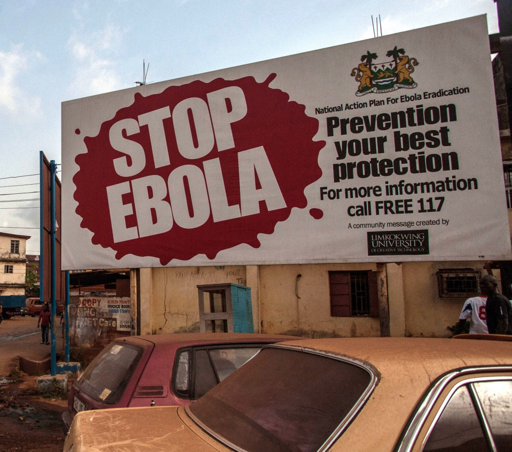 FILE- In this file photo taken on Friday, Jan. 15, 2016, people pass a banner reading 'STOP EBOLA' forming part of Sierra Leone's Ebola free campaign in the city of Freetown, Sierra Leone. A second case of Ebola emerged Thursday Jan. 21, 2016 in Sierra Leone after health officials thought the epidemic was over, with a close relative of the first victim testing positive for the virus that has killed more than 11,000 people, authorities said. (AP Photo/Aurelie Marrier d'Unienville,File)
