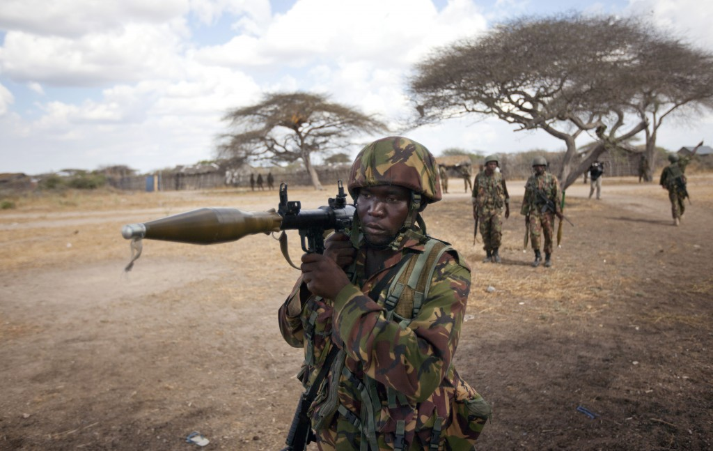 FILE - In this Monday, Feb. 20, 2012 file photo, a Kenyan army soldier carries a rocket-propelled grenade launcher as he patrols in Tabda, inside Somalia. Heavily armed fighters from the Islamic extremist group al-Shabab attacked a base for African Union peacekeepers in southwestern Somalia on Friday, Jan. 15, 2016, blasting their way into the compound and exchanging fire with peacekeepers, a Somali military official said. (AP Photo/Ben Curtis, File)