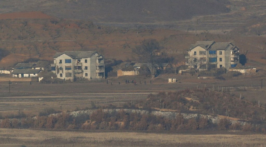 """North Koreans walk at their town Kaepoong, viewed from the unification observatory in Paju, north of Seoul, South Korea, Thursday, Jan. 7, 2016. The United States, South Korea and Japan agreed to launch a """"united and strong"""" international response to North Korea's apparent fourth nuclear test, as experts scrambled Thursday to find more details about the detonation that drew worldwide skepticism and condemnation. (AP Photo/Lee Jin-man)"""