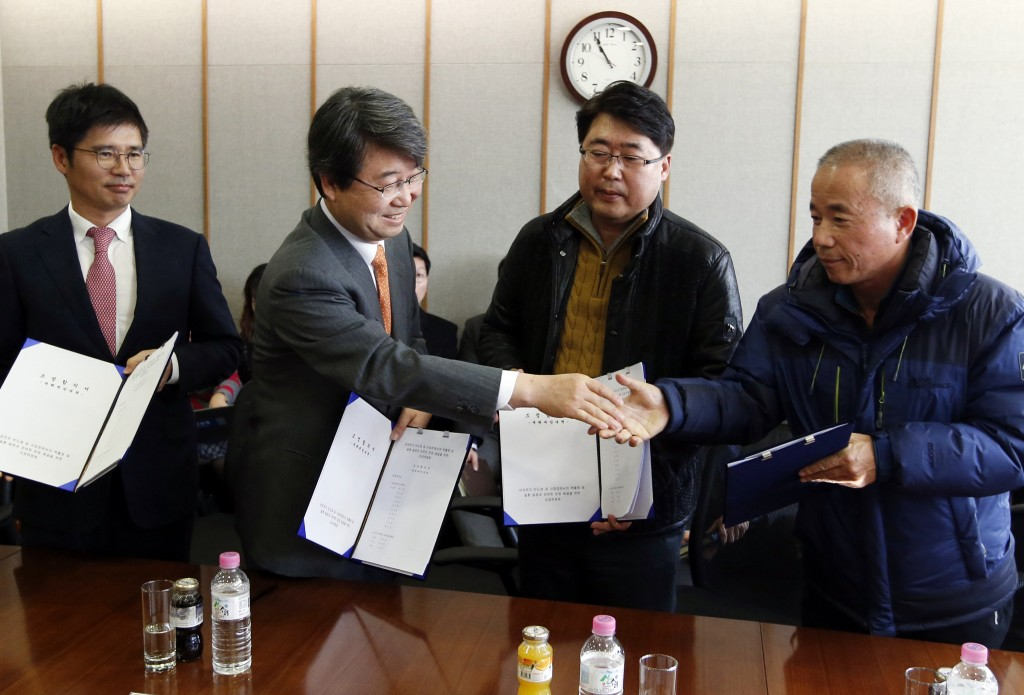 Kim Ji-hyung, center left, a chairman of the Mediation Committee, shakes hands with Hwang Sang-gi, right, father of former Samsung semiconductor factory worker Hwang Yu-mi, who died from leukemia in 2007,  as Baek Suhyeon, left, a senior vice president at Samsung Electronics, and other family members look on after they reached a partial agreement in Seoul on Tuesday. (AP Photo/Lee Jin-man, Pool)