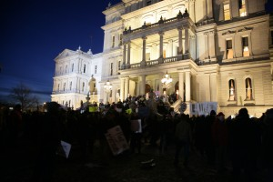 Protesters gather outside the state Capitol in Lansing before Michigan Gov. Rick Snyder's State of the State address, Tuesday evening. (AP Photo/Al Goldis)
