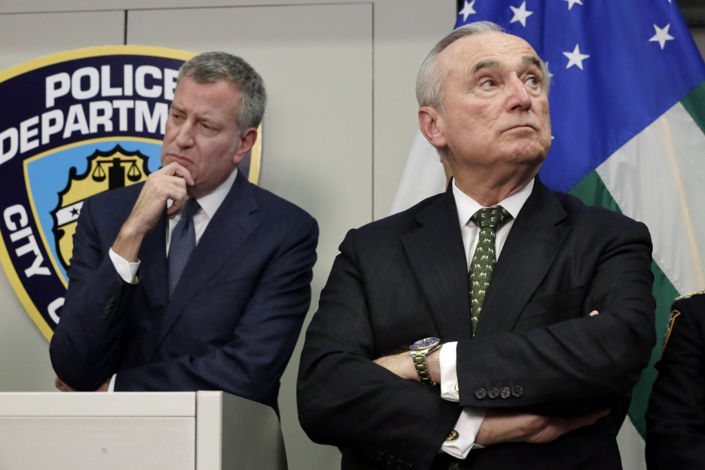Mayor Bill de Blasio (L) and Police Commissioner William Bratton listen Monday as crime statistics are presented during a news conference at police headquarters. (AP Photo/Richard Drew)
