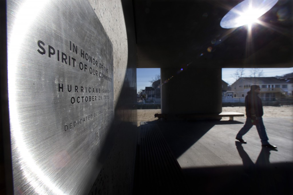 """A plaque on the monument to Superstorm on the beach in Highlands, N.J. The borough is demanding that a trade group remove a monument to the survivors of Superstorm Sandy. A Highlands attorney sent a letter to the Tilt-Up Concrete Association Monday asking the group to remove a more than 1,000-square-foot monument from the beach. The monument, dubbed """"Shorehenge,"""" has been questioned by residents for its aesthetics. (AP Photo/Mel Evans)"""