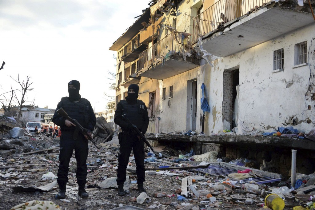 Turkish police officers secure a destroyed police station in Cinar in the mostly-Kurdish Diyarbakir province in southeastern Turkey Thursday, Jan. 14, 2016. Kurdish rebels detonated a car bomb at a police station in southeastern Turkey, then attacked it with rocket launchers and firearms, killing several people, including civilians, the governor's office said Thursday. (Ahmet Un/DHA via AP) TURKEY OUT