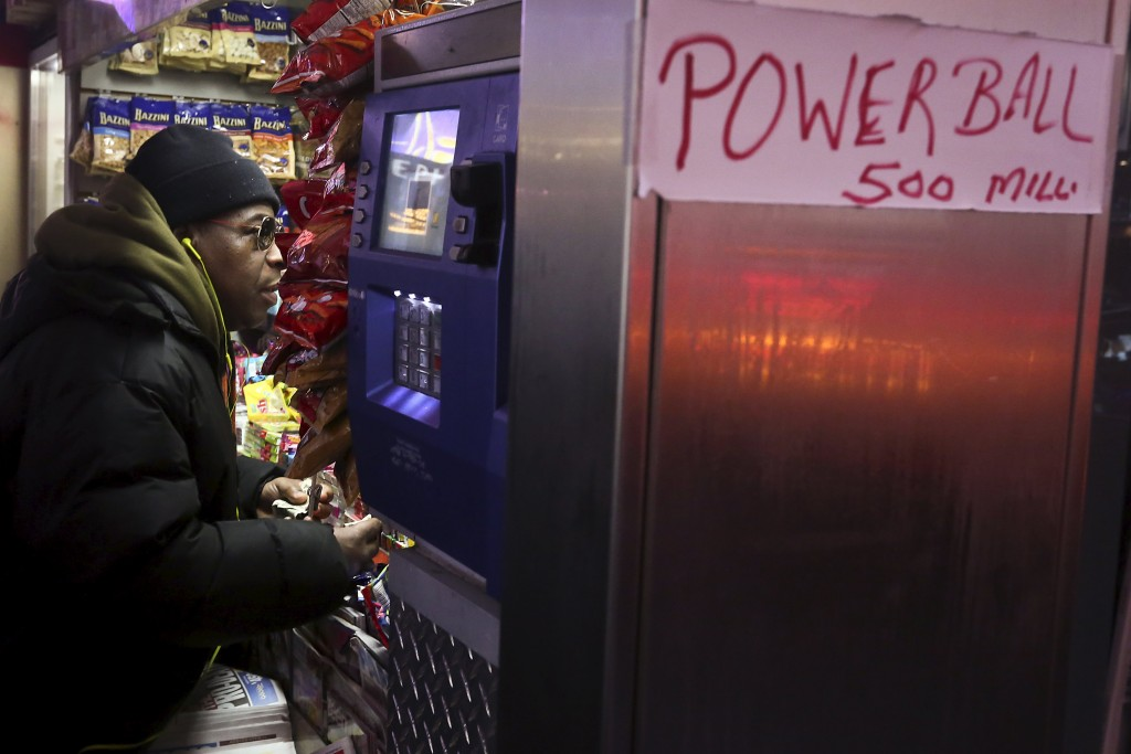 A man purchases tickets for the $500 million Powerball lottery draw in Times Square in the Manhattan borough of New York, January 6, 2016. REUTERS/Carlo Allegri
