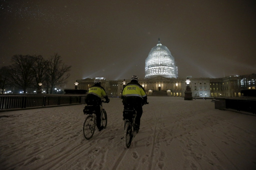 U.S. Capitol Police officers patrol on their bicycles in the snow at the U.S. Capitol in Washington January 20, 2016. REUTERS/Jonathan Ernst