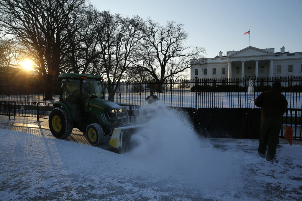 Workers plow snow from the sidewalk in front of the White House in Washington January 21, 2016. REUTERS/Jonathan Ernst
