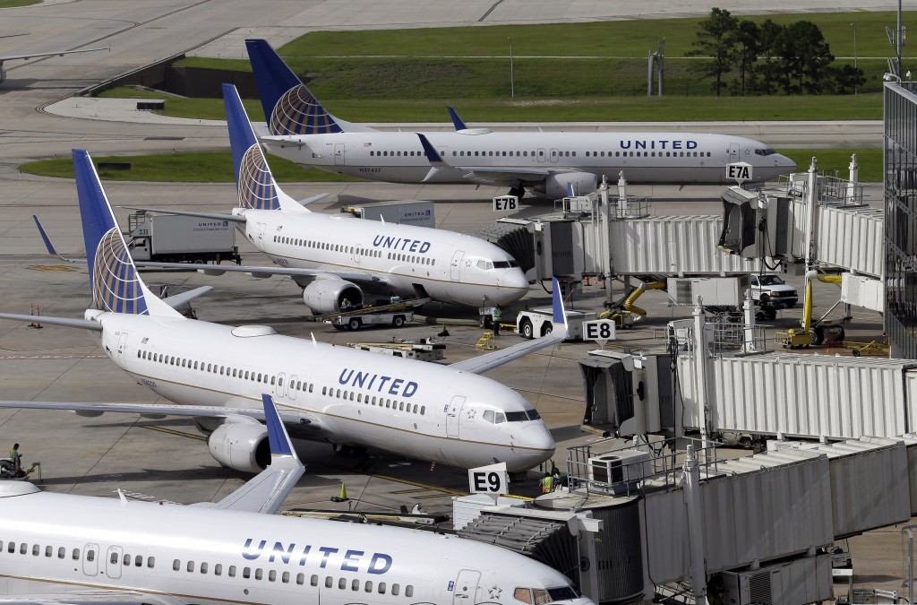 FILE - In this July 8, 2015, file photo, United Airlines planes are parked at their gates as another plane, top, taxis past them at George Bush Intercontinental Airport, in Houston. (AP Photo/David J. Phillip, File)