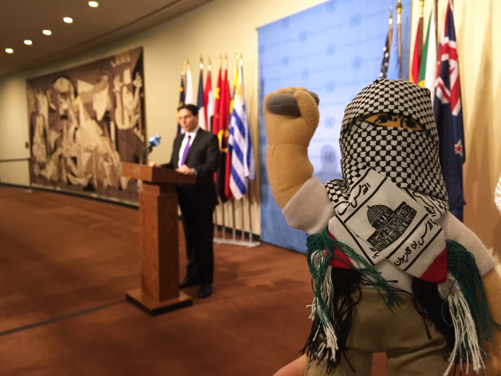 """Israel's U.N. Ambassador, Danny Danon, speaking at the U.N. on Tuesday, as a """"terror dolls"""" - like those being used to teach hatred among Palestinian children - is displayed nearby. (AP Photo/Cara Anna)"""