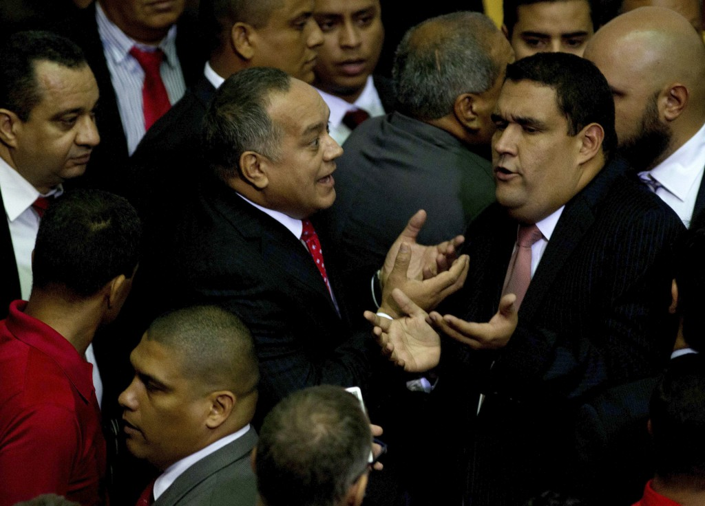 Diosdado Cabello, outgoing parliamentary president, center left, argues with an opposition congressmen prior to leaving the National Assembly in Caracas, Venezuela, on Tuesday. (AP Photo/Fernando Llano)